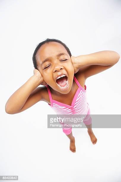 High angle shot of young girl holding ears and shouting