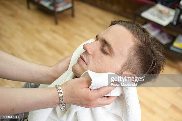 High angle side view of young man in barbershop, head back, eyes closed having face dried with towel