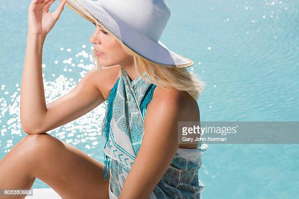 High angle side view of young woman wearing sun hat sitting by swimming pool