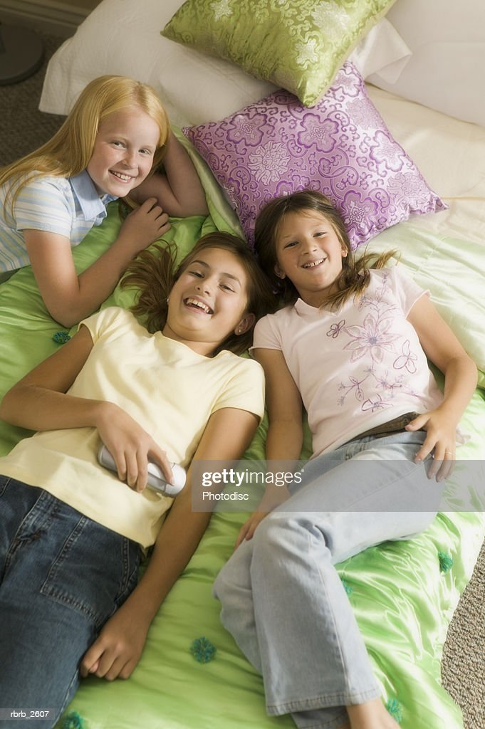 high angle teenage lifestyle shot of three girls as they lay on the bed and smile : Foto de stock