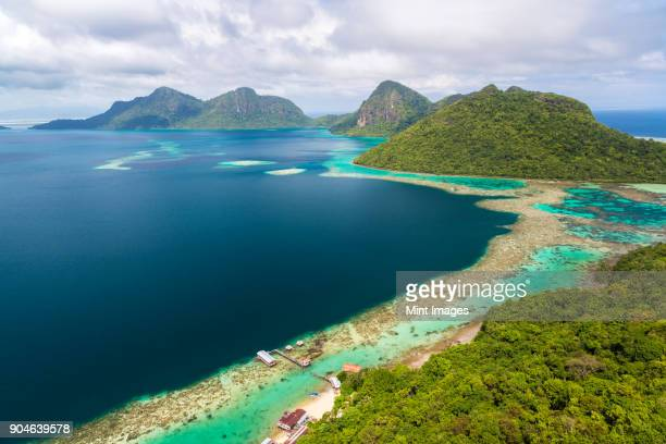 high angle view along coastline of tropical island, mountains in the distance. - island of borneo stock pictures, royalty-free photos & images