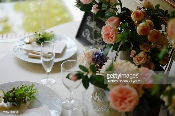 High Angle View Artificial Flower Decorations By Wineglass And Plate On Table