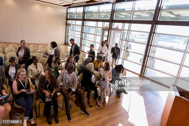 high angle view as conference attendees wait for speaker - town hall meeting stock pictures, royalty-free photos & images