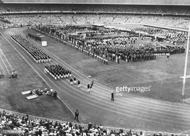 High angle view as one of the competing nations walk the track, following the flagbearer at the opening ceremony at the 1956 Summer Olympics, at...