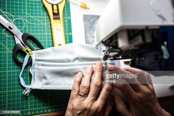 high angle view close-up of mature woman sewing protective face masks during coronavirus pandemic - preparation stock pictures, royalty-free photos & images