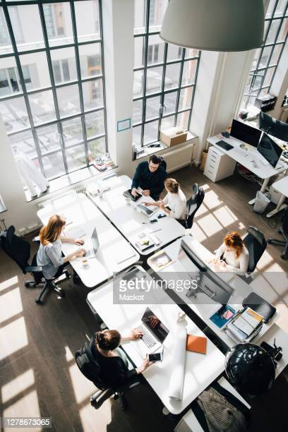 high angle view colleagues working at table in new workplace - coworking stock pictures, royalty-free photos & images