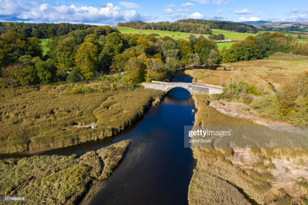 High angle view from a drone of an old stone bridge crossing a river in Dumfries and Galloway south west Scotland : Stock Photo