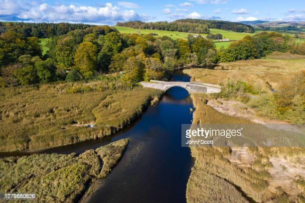 high angle view from a drone of an old stone bridge crossing a river in dumfries and galloway south west scotland - johnfscott stock pictures, royalty-free photos & images