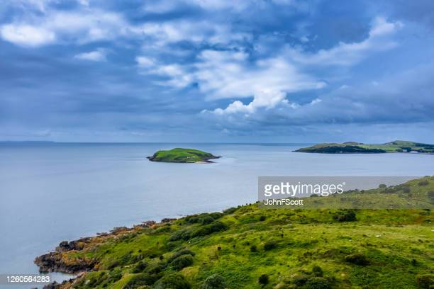 high angle view looking out towards a small island and the surrounding sea in south west scotland - johnfscott stock pictures, royalty-free photos & images