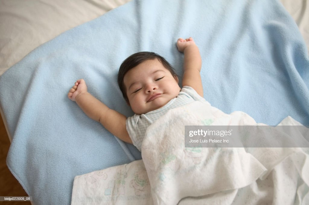 High angle view of a baby boy sleeping on a bed : Stock Photo