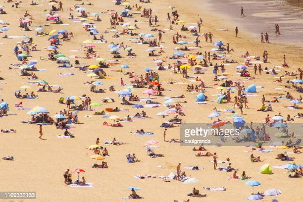 high angle view of a beach full of people, beach of barinatxe, la salvaje. - naturists stock pictures, royalty-free photos & images