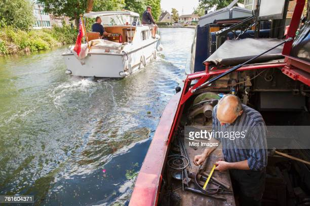 High angle view of a blacksmith working at his bench on a narrowboat on the water, holding a tape measure. A motorboat underway.
