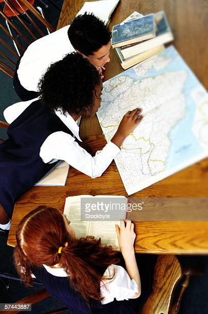 high angle view of a boy and girl (8-10) studying a map at the library