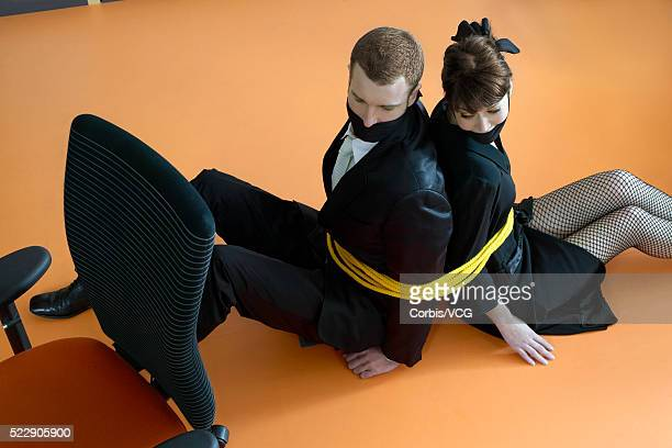 High angle view of a businessman and a businesswoman tied up and gagged
