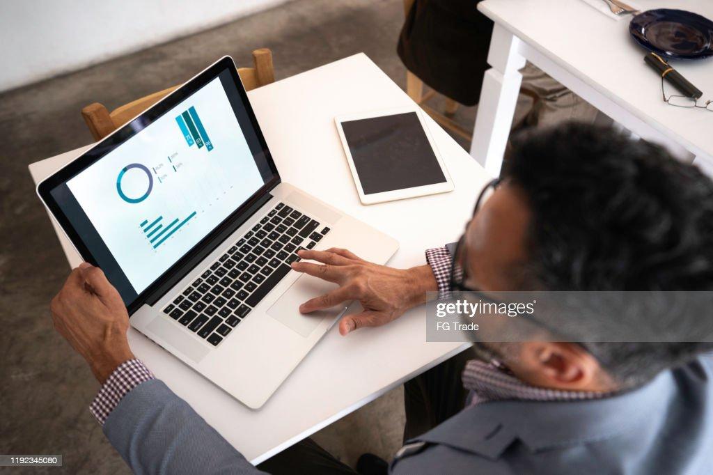 Groothoekbeeld van een zakenman die laptop in een restaurant gebruikt : Stockfoto