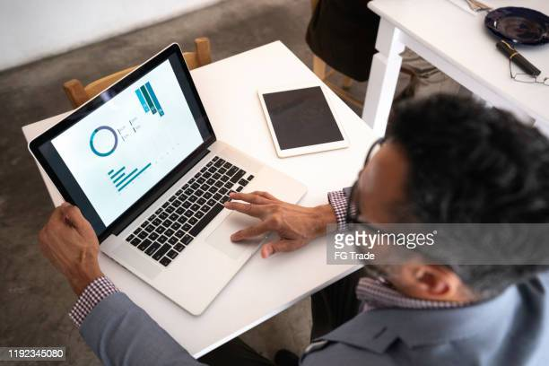 high angle view of a businessman using laptop in a restaurant - device screen stock pictures, royalty-free photos & images