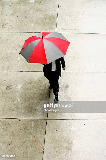 High angle view of a businessman walking with an umbrella