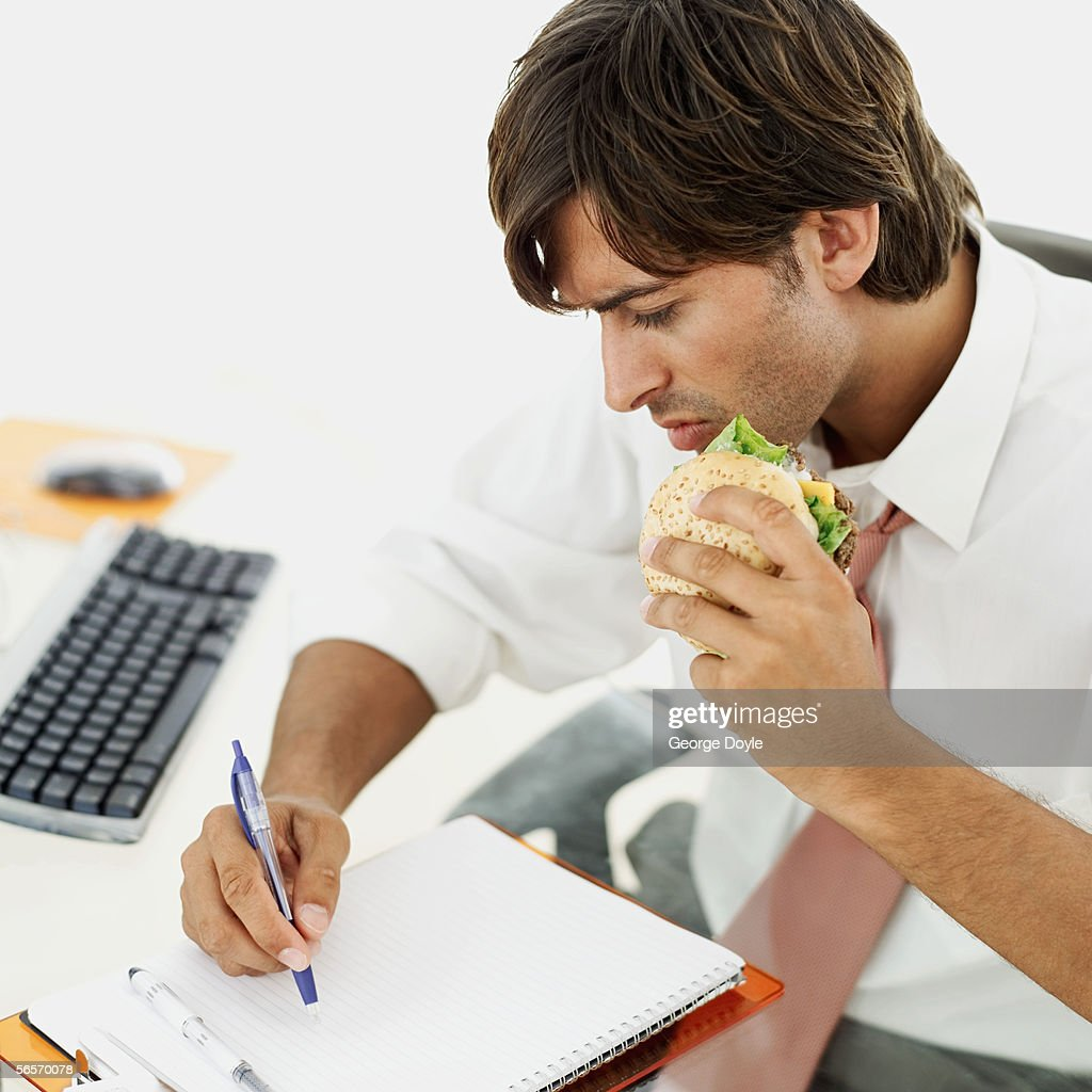high angle view of a businessman writing on notebook while eating a burger : Stock Photo