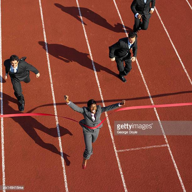 high angle view of a businesswoman crossing the finish line ahead of businessmen