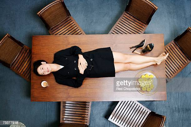 High angle view of a businesswoman lying on the table