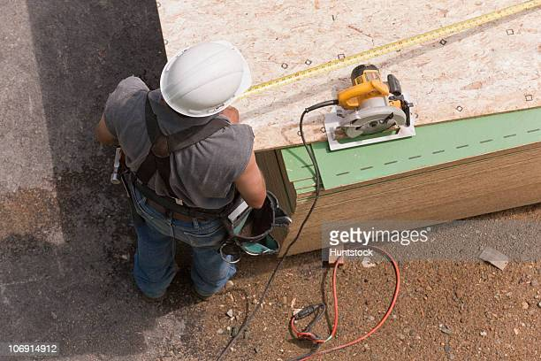 High angle view of a carpenter measuring floor panels at a construction site