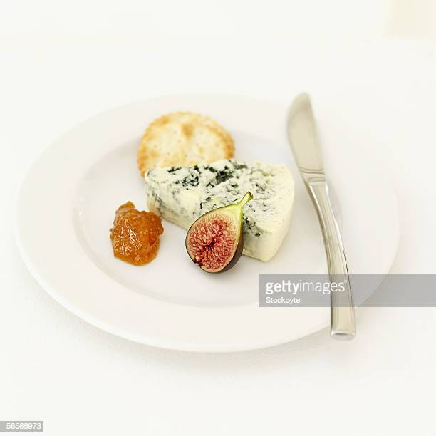 high angle view of a cheese knife with crackers and fruit on a plate
