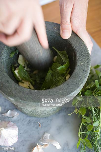 High Angle View of a Chef Using a Mortar and Pestle To Grind Together Garlic and Herbs