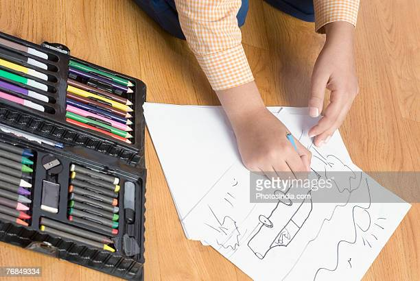High angle view of a child's hand drawing a picture on a sheet of paper