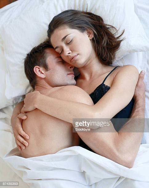 high angle view of a couple asleep holding each other - romantic young couple sleeping in bed stock photos and pictures