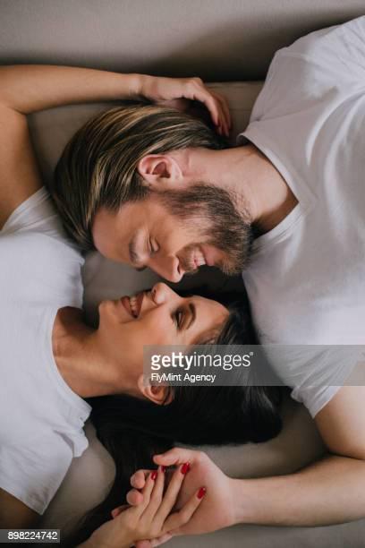 Vogelperspektive Blick auf ein paar auf einem Bett liegend und wandte sich an einander
