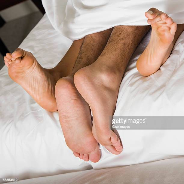 High angle view of a couple's feet under the sheets of a bed