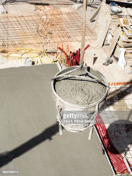 High angle view of a  crane with a vat of concrete the air, on the foundations of a building in construction. Spain
