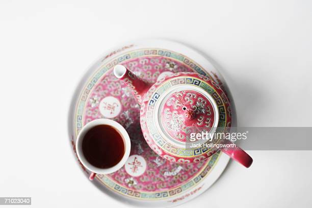 High angle view of a cup of black tea and a teapot on a tray