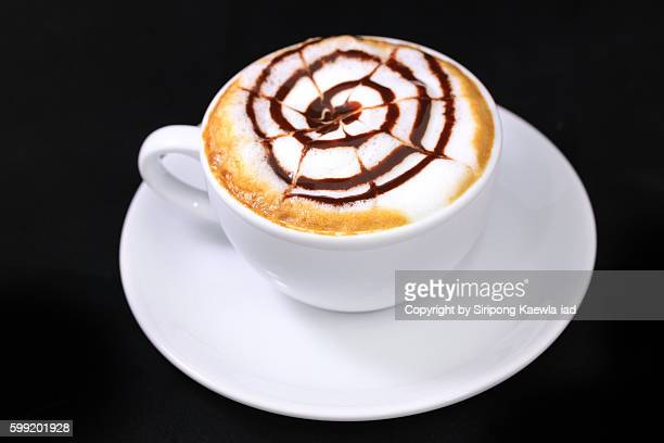 High angle view of a cup of coffee latte with cream and chocolate sauce.