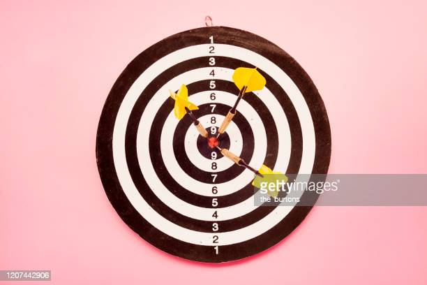 high angle view of a dartboard and three yellow darts on pink colored background - aiming stock pictures, royalty-free photos & images