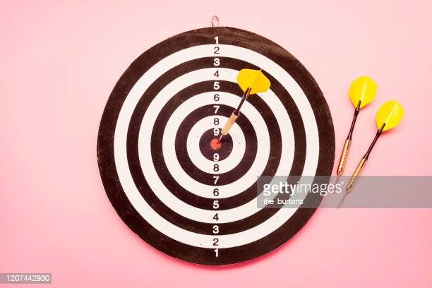 high angle view of a dartboard and three yellow darts on pink colored background - point scoring stock pictures, royalty-free photos & images