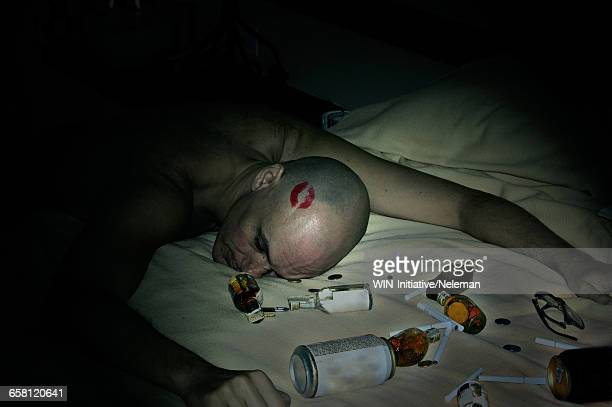 high angle view of a drunk man with red lipstick mark on his head - after party stock pictures, royalty-free photos & images