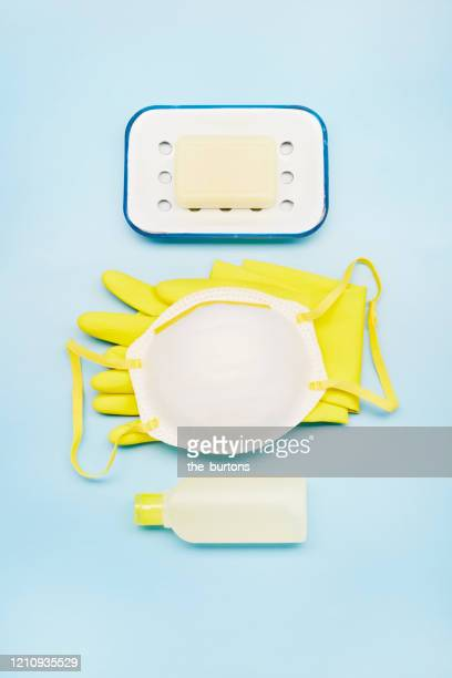 high angle view of a face mask, protective glove, soap and bottle of detergent on blue background - medical condition stock pictures, royalty-free photos & images