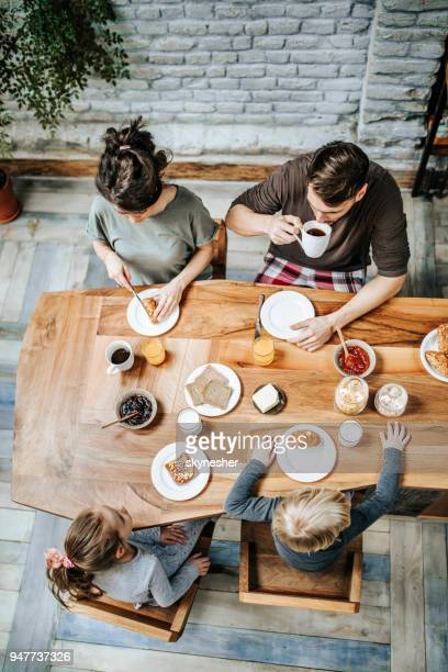 high angle view of a family eating their breakfast together at dining table. - domestic kitchen stock pictures, royalty-free photos & images