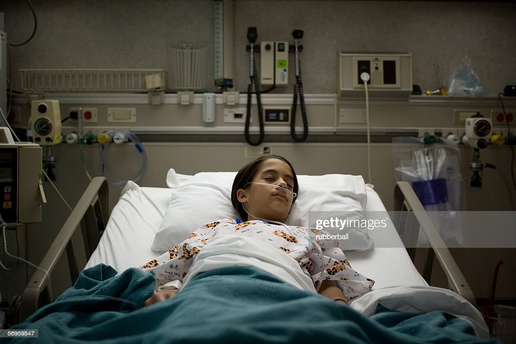 High angle view of a female patient sleeping on a hospital bed : Stock Photo