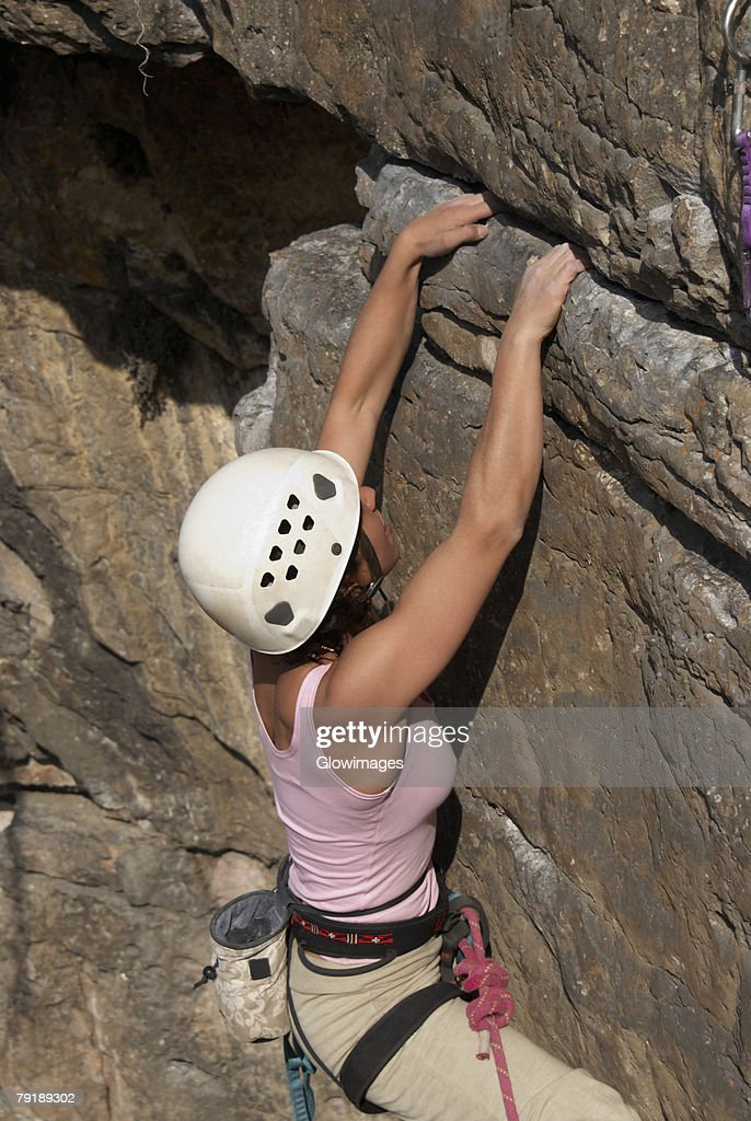 High angle view of a female rock climber scaling a rock face : Foto de stock