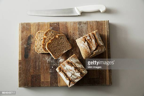 High angle view of a freshly baked loaf of bread and slices on a wooden chopping board, a bread knife.