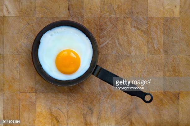 high angle view of a fried egg in a pan - fried eggs stock pictures, royalty-free photos & images