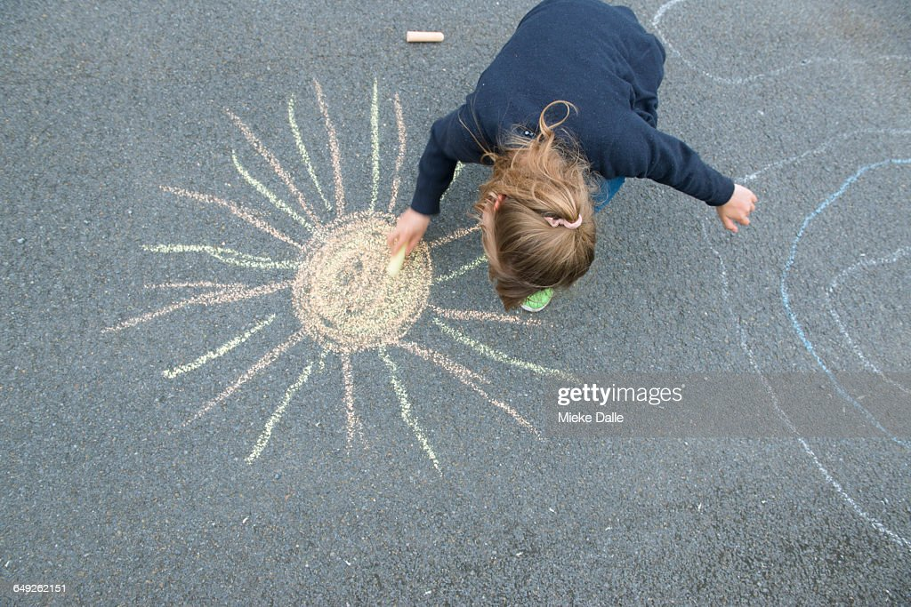 High Angle View Of A Girl Drawing On Street : Stock Photo