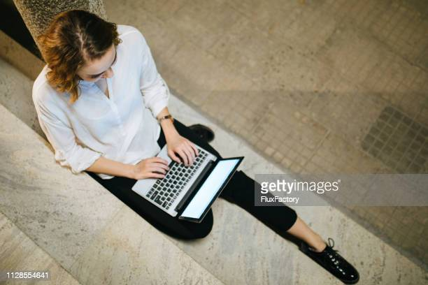 high angle view of a girl sitting on staircase using laptop - digital marketing foto e immagini stock