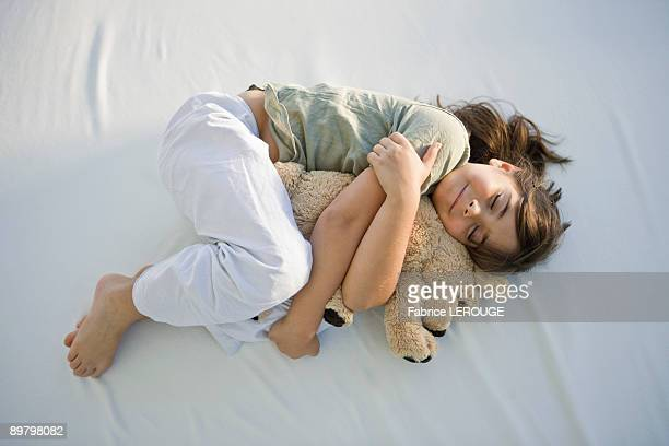 High angle view of a girl sleeping with a teddy bear