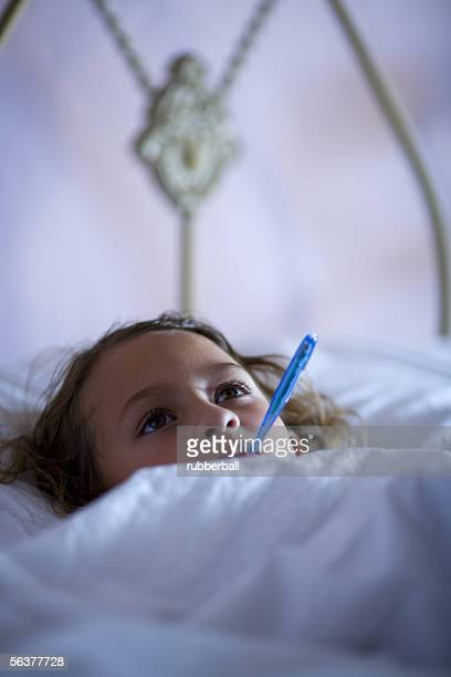 High angle view of a girl with a thermometer in her mouth