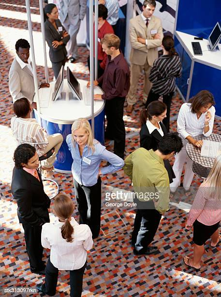 high angle view of a group of business executives at an exhibition - tradeshow stock pictures, royalty-free photos & images