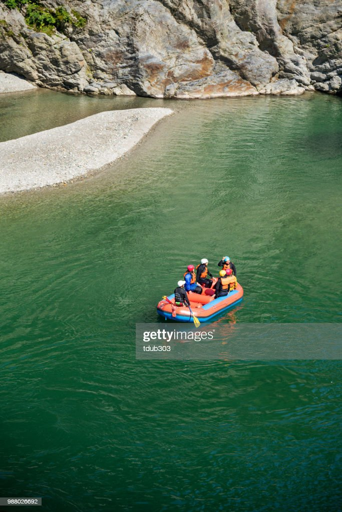 High angle view of a group of men and women heading to or from  shore while rafting : Stock Photo