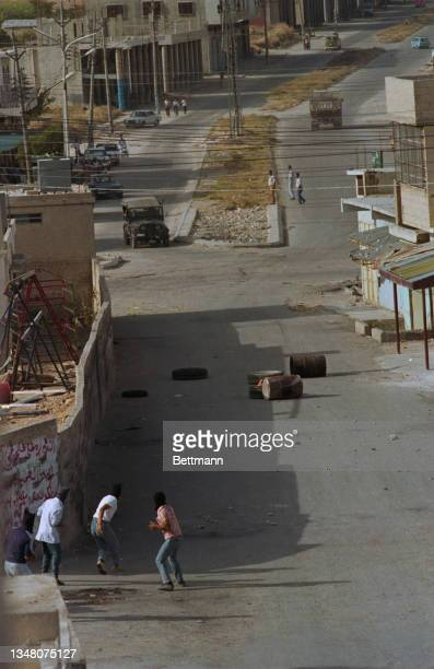 High angle view of a group of youths, throwing objects at a military Jeep in the distance, barrels discarded in the road, in an unspecified area of...